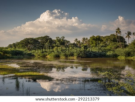Thanjavur, India - October 14, 2013: Evening storm gathers over the jungle along the Vennar River. Clouds reflected in the water around sand banks. - stock photo