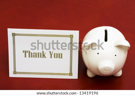 Thank you card and piggy bank with copy space - stock photo