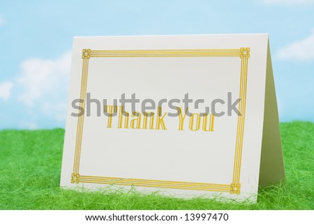 Thank you card on grass with sky background - stock photo