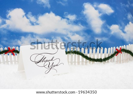Thank you card sitting on snow with white fence and green garland on a sky background - stock photo