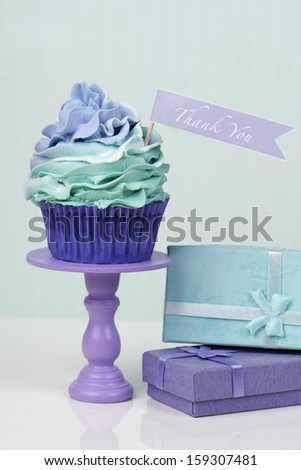 Thank you cupcake on cake stand with presents - stock photo