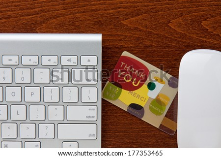 Thank you gift card in between keyboard and mouse on a brown wooden grain desktop. - stock photo