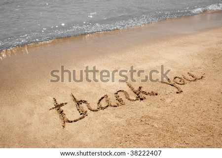 Thank you handwritten in sand on a beach - stock photo