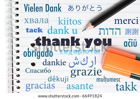 Thank you in many different languages written on an open notebook - stock photo