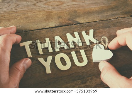 thank you letters and men's hand over wooden table. vintage filtered and toned - stock photo