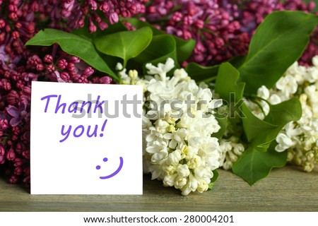 Thank you note and lilac flower on the wooden table - stock photo