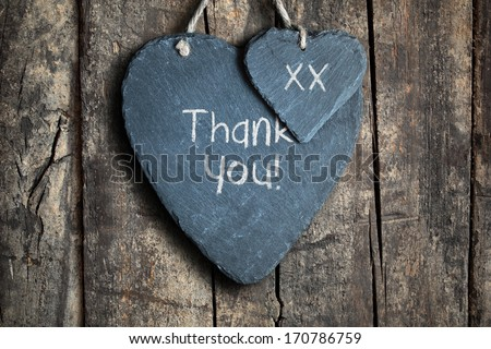 Thank you note written in chalk on a slate heart hanging on a wooden background - stock photo