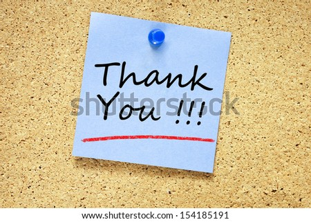 Thank You on blue sticky note pinned with blue push pin on cork board  - stock photo