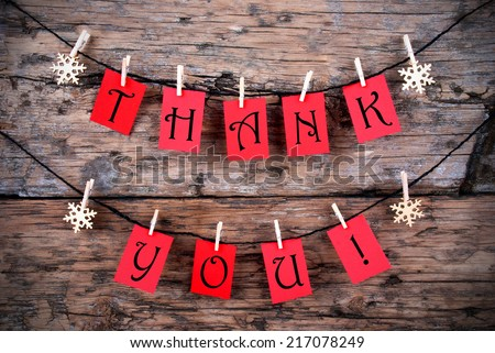 Thank You on Red Tags Hanging on a Line in front of a wooden Background - stock photo