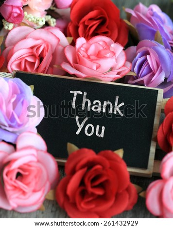 thank you sign on chalkboard, with flowers in background - stock photo