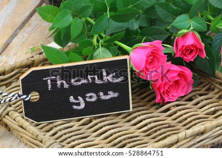 Thank you written on mini blackboard with one pink rose on wicker tray