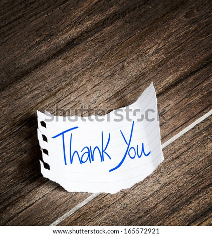 Thank You written on the paper on a wood background - stock photo