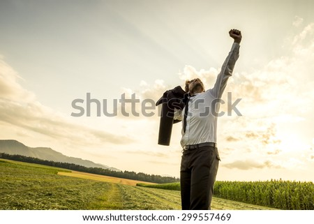 Thankful Young Businessman Standing in the Green Field and Raising his Arm While Looking Up the Sky for Success. - stock photo