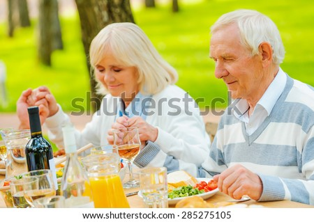 Thanking for the meal. Senior couple holding hands and praying before family dinner while sitting at the table outdoors  - stock photo