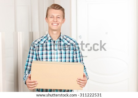 Thanks for service. Pleased handsome nice man holding parcel and standing on the porch while evincing joy. - stock photo