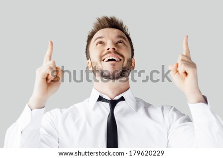 Thanks to God! Handsome young man in shirt and tie pointing up and smiling while standing against grey background - stock photo