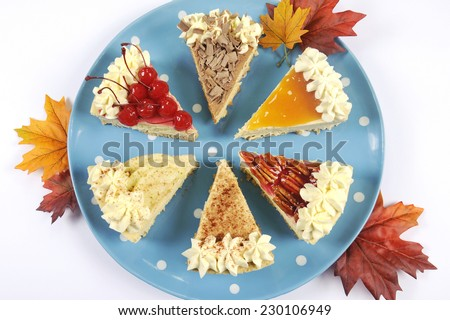 Thanksgiving apple, pecan, cherry, caramel, pumpkin spice and chocolate cream cheesecake pie, on blue polka dot platter against a white table, with autumn fall leaves. - stock photo