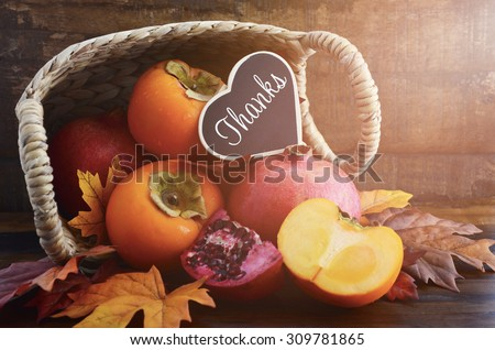 Thanksgiving Autumn feast fruit, with persimmons and pomegranates tumbling out of a basket with Thanks message on a rustic wood background, and added filters and lens flare light stream.  - stock photo