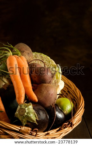 Thanksgiving basket filled with autumn fruits and vegetables on table with mottled background. - stock photo