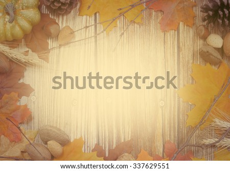 Thanksgiving border of autumn leaves, bare twigs, pinecones, wheat stalks and nuts with rustic wooden background in center. Copy space. Vintage filter applied for artistic purposes - stock photo