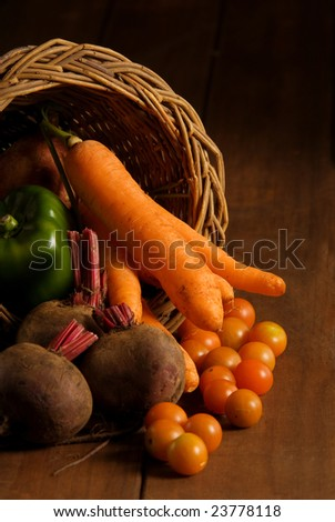 Thanksgiving cornucopia filled with autumn fruits and vegetables on wooden table. - stock photo