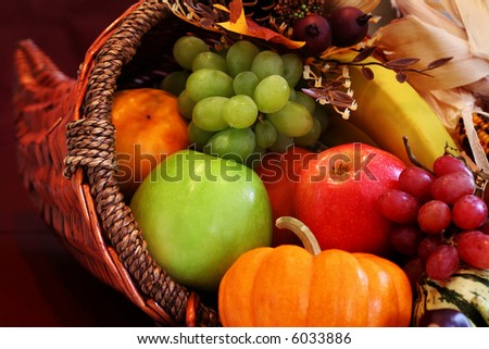 Thanksgiving cornucopia filled with autumn fruits and vegetables. Shallow DOF with focus on basket edge.