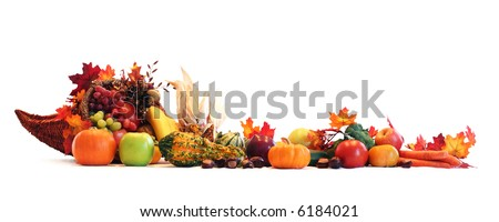 Thanksgiving cornucopia filled with autumn fruits and vegetables spread out to create a border.