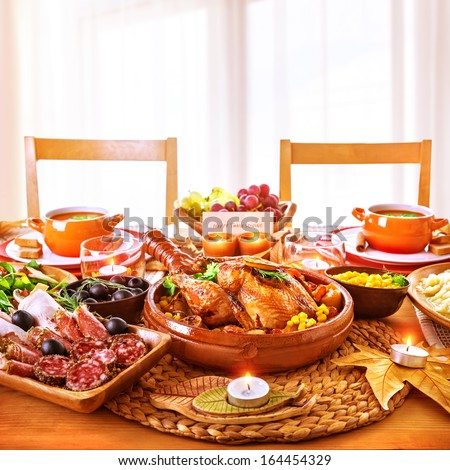 Thanksgiving day dinner, tasty baked chicken on centerpiece of festive table, cold cuts, candle light, greeting card, happy holiday celebration - stock photo