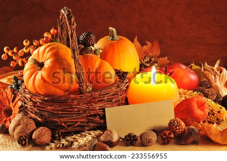 Thanksgiving - different pumpkins, nuts, maize cob and apple in rattan basket with candlelight and copyspace