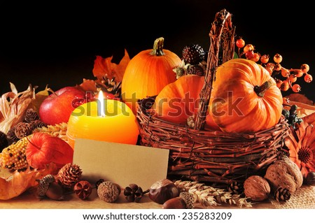 Thanksgiving - different pumpkins, nuts, maize cob and apple in rattan basket with candlelight and copyspace - stock photo