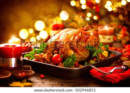 Thanksgiving dinner, Thanksgiving turkey. Served table. Thanksgiving table served with turkey, decorated with bright autumn leaves. Roasted turkey, table setting
