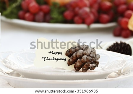 """Thanksgiving Holiday place setting with a """"Happy Thanksgiving"""" note card placed on plate held in place by a pine cone. Extreme shallow depth of field with selective focus on card. - stock photo"""