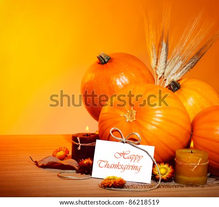 Thanksgiving holiday, pumpkin border still life decoration with candles and wheat over yellow studio light background, greeting card with text space, harvest concept - stock photo