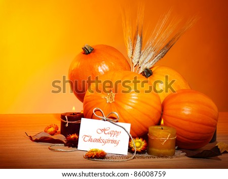 Thanksgiving holiday, pumpkin still life decoration with candles and wheat over yellow studio light background, greeting card with text space, harvest concept - stock photo