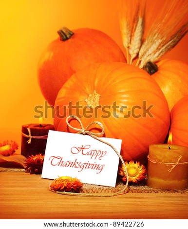 Thanksgiving holiday, pumpkin still life decoration with candles on the wooden table over yellow light background, greeting card with text space, harvest concept - stock photo