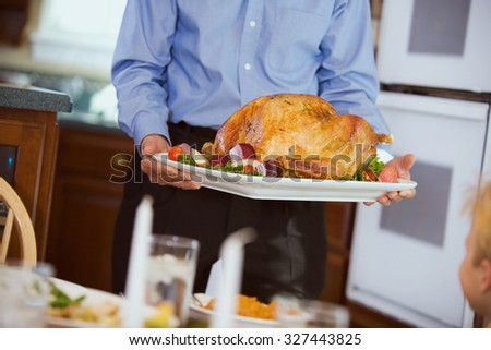 Thanksgiving: Roast Turkey Brought To Table On Platter - stock photo