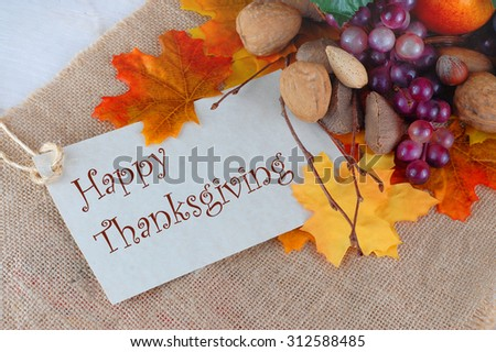 Thanksgiving scene of cornucopia overflowing with purple grapes, a pear, and orange and nuts with golden autumn leaves scattered around and a Happy Thanksgiving message on burlap background - stock photo