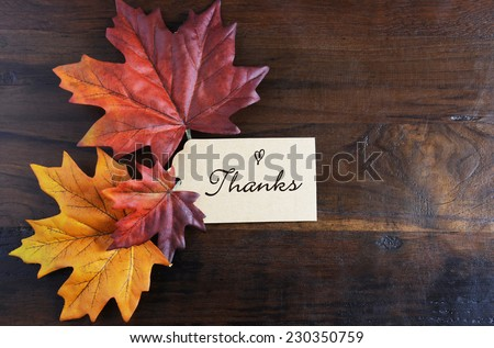 Thanksgiving table place setting with greeting tag and autumn fall leaves on rustic dark recycled wood background, with copy space. - stock photo