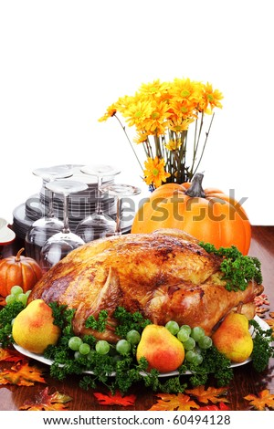 Thanksgiving turkey dinner with fresh fruit, dishes and flowers. - stock photo