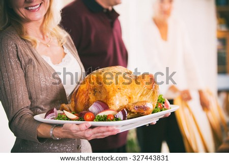 Thanksgiving: Woman Holding Platter With Roast Turkey And Garnish - stock photo