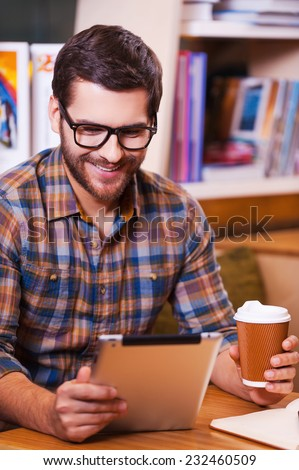 That is just amazing! Happy young man holding coffee cup and looking at his digital tablet while sitting at the desk with bookshelf in the background - stock photo