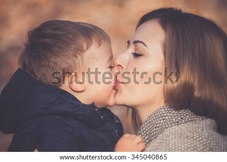 that is the sweet loving kiss, mom and sun kissing, beautiful autumn day, closeup, selective focus - stock photo