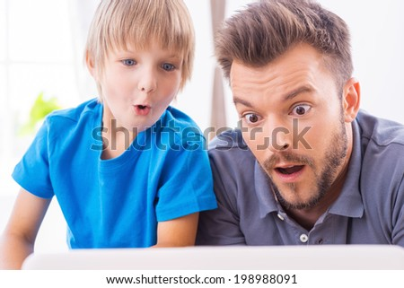 That is unbelievable! Surprised father and son looking at the laptop and keeping mouth open - stock photo