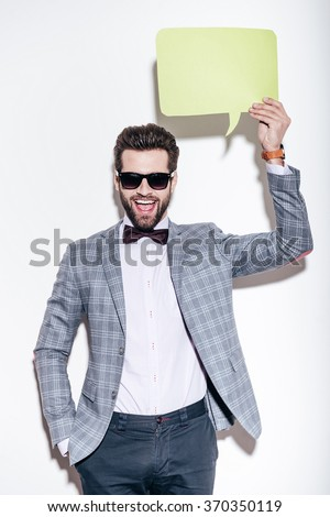 That is what I am saying. Handsome young cheerful man in suit looking at camera with smile and holding green speech bubble upon his head while standing against white background - stock photo