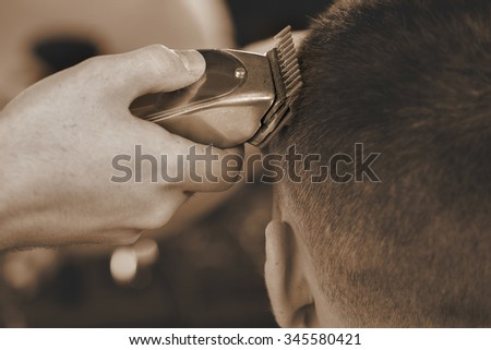 That is what trimmers are for. Closeup shot of a barber using trimmer while giving a haircut to his male client