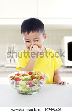 That smells bad! Young asian child covering his nose from vegetables. shot in kitchen - stock photo