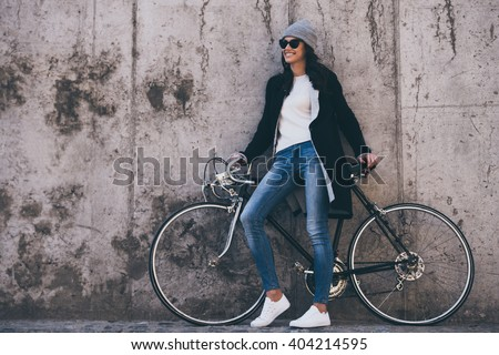 That was great ride! Beautiful young woman in sunglasses holding hands on her bicycle and looking away with smile while standing against concrete wall outdoors - stock photo