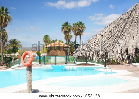 Thatch parasol with swimming pool background - stock photo