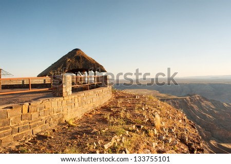 Thatch shelter next to steep - sunset. Shot in Fish River Canyon National Park, Namibia. - stock photo