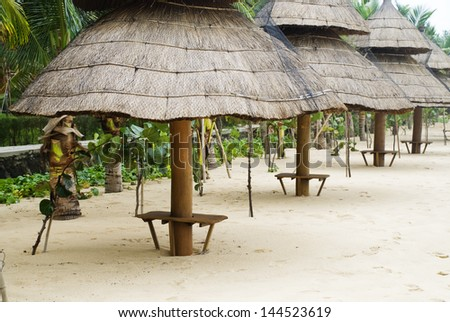 Thatched beach shelters on a tropical Asian beach. - stock photo